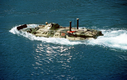 A BTR-80 swimming ashore from a tank landing ship