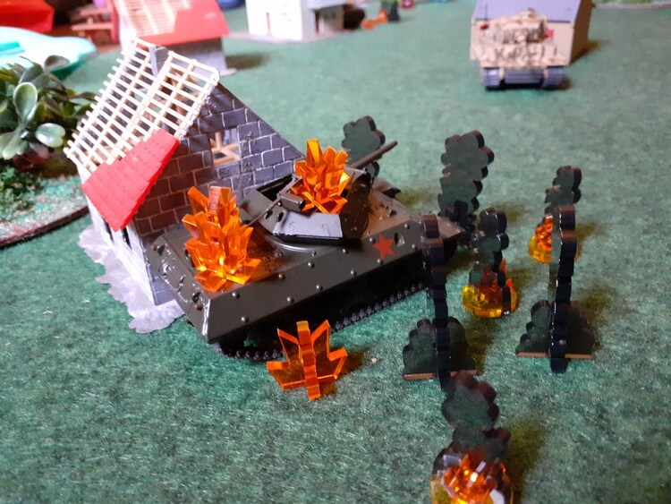 Photo of a Panzer Kids game. A model M10 tank destroyer is next to a model house and surrounded by smoke and blast markers. More buildings and a Tiger tank are visible in the background.
