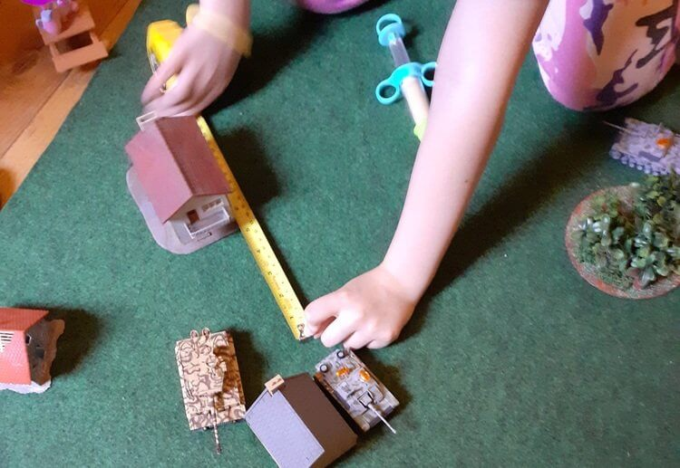 Photo of a Panzer Kids game. A player is using a tape measure to measure a model StuG's movement. Also visible are a model Tiger tank, buildings and a wood.