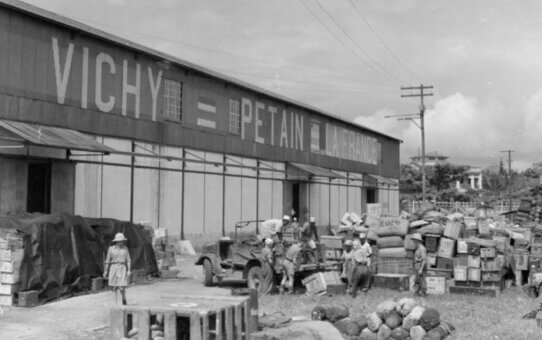 """Photo of warehouse with stores outside. The warehouse has """"VICHY = PETAIN = LA FRANCE"""" painted on it."""