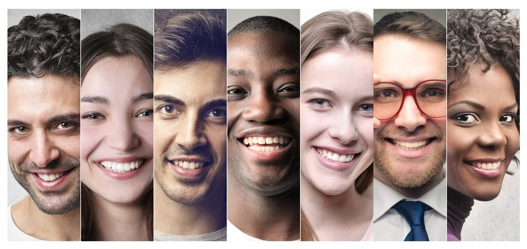 Seven smiling people of diverse genders and races